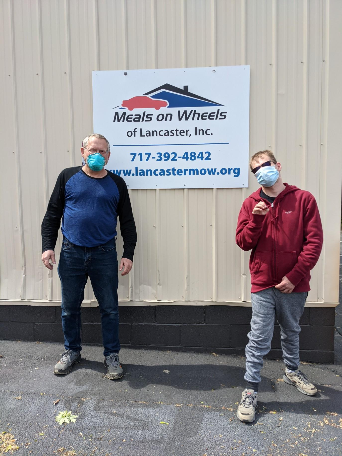 meals on wheels volunteers standing in front of a sign